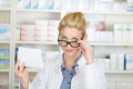 Pharmacist With Prescription Looking Over Glasses