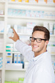 Male Pharmacist With Drug Package At Drugstore
