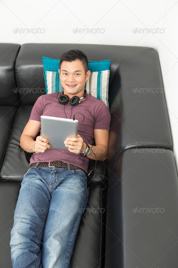 Chinese man sitting on sofa using Digital Tablet