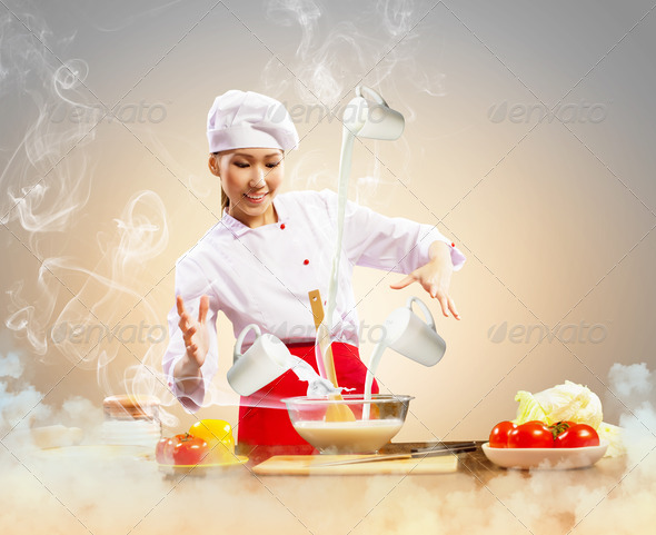 Asian female cooking with magic - Stock Photo - Images