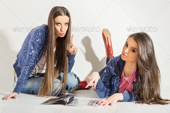 Beautiful young fashionable girls reading magazine - Stock Photo - Images