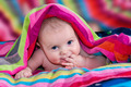 Beautiful Baby with Finger in Mouth Comes Out From a Colorful Blanket - PhotoDune Item for Sale