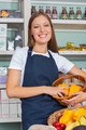 Saleswoman Holding Vegetable Basket In Grocery store