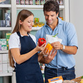 Saleswoman Assisting Male Customer At Grocery Store