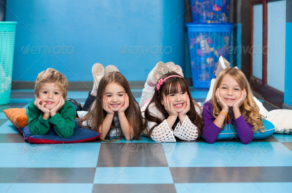 Children Lying In A Row On Floor In Classroom - Stock Photo - Images