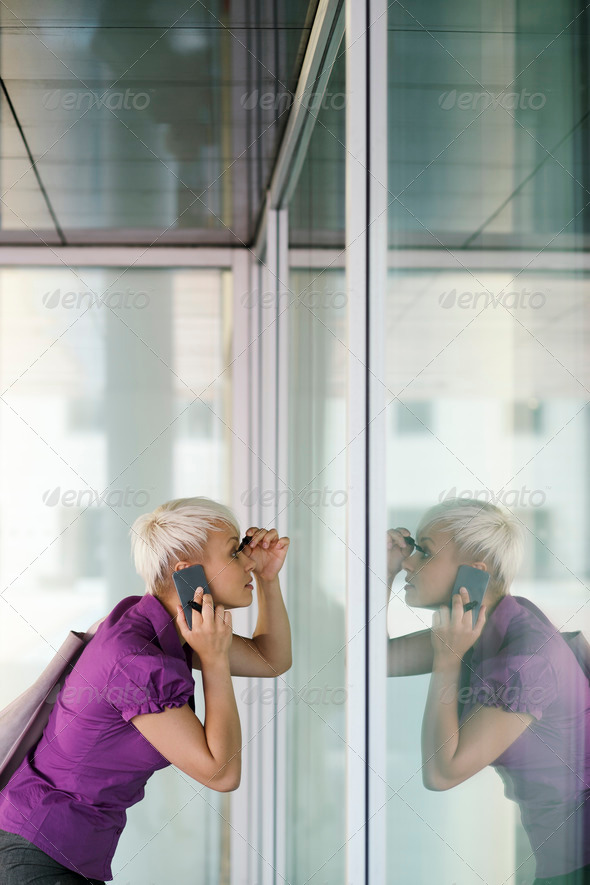 young business woman applying makeup in the street - Stock Photo - Images