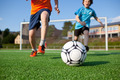 Boys Playing Football On Field