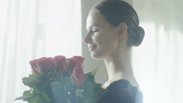 VideoHive Gorgeous Young Ballet Dancer Holding and Sniffing Bouquet of Red Roses 19473676