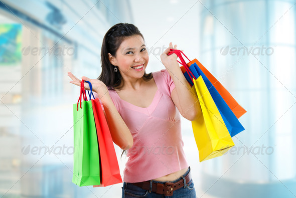 Happy Asian shopping woman smiling holding many shopping bags at the mall. Casual Asian shopper girl standing in department store. Beautiful mixed race Caucasian Southeast Asian woman model.