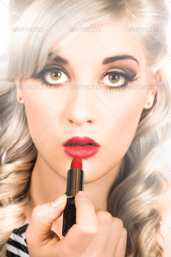 Sexy retro pinup girl applying makeup on lips - Stock Photo - Images