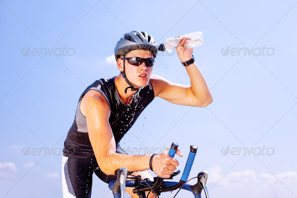 Triathlete cycling on a bicycle - Stock Photo - Images