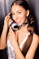 Club style woman with headphones listening to music looking at camera. Against wall. Copyspace