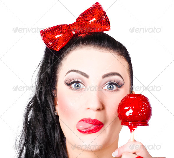 Sweet pin-up girl eating a candy toffee apple - Stock Photo - Images