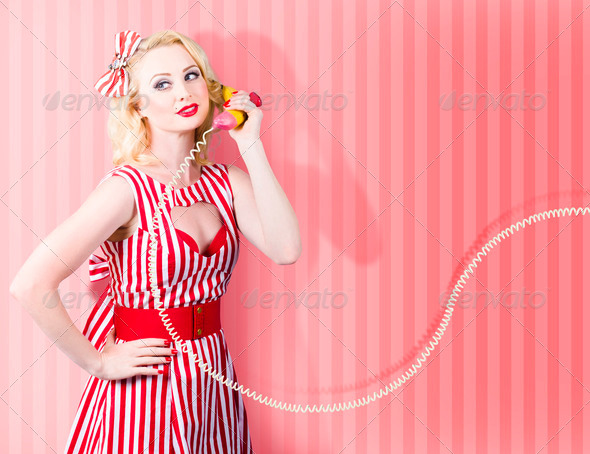 Retro housewife in 50s fashion on vintage phone - Stock Photo - Images