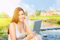 Cute young brunette using tablet computer sitting by the river - PhotoDune Item for Sale