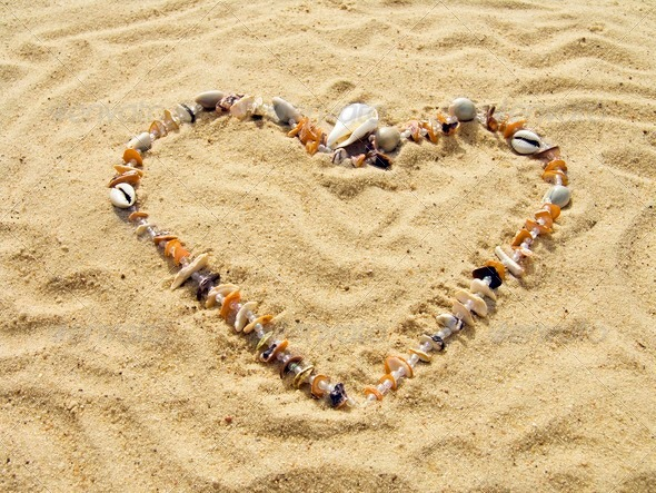 Heart from cockleshells and sea pebbles - Stock Photo - Images