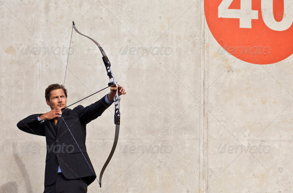 Businessman aiming bow and arrow at target