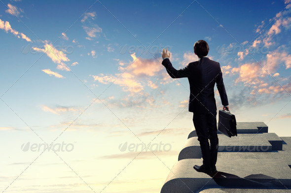 Businessman on top of building - Stock Photo - Images