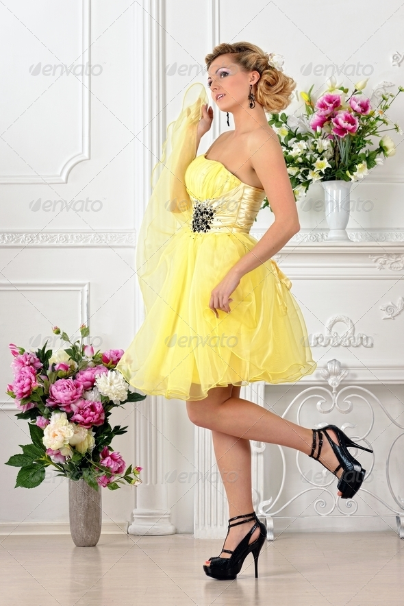 Beautiful woman in yellow dress in luxury studio. - Stock Photo - Images