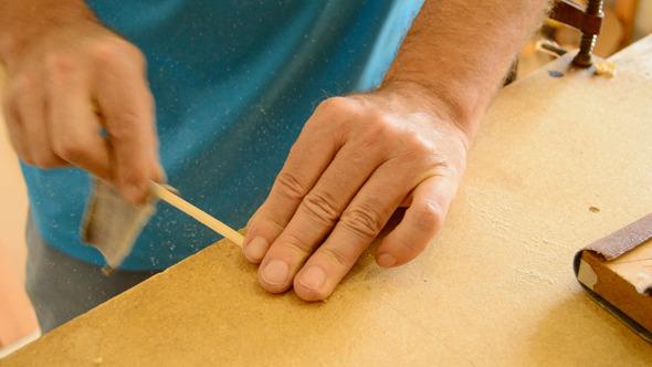 Luthier Sanding a Guitar Piece