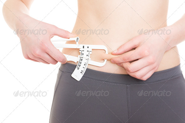 Woman measuring her body fat on abdomen using caliper - Stock Photo - Images