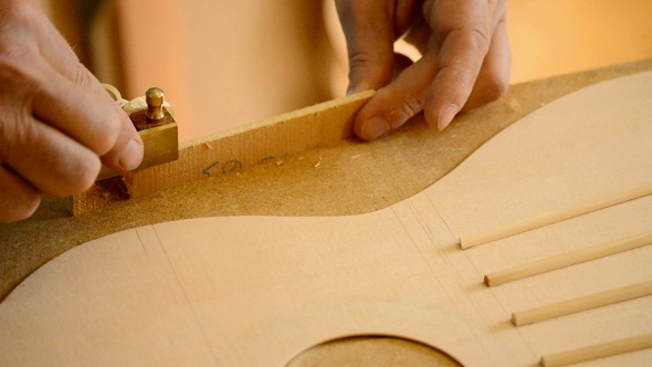 Luthier Working on a Guitar Harmonic Cover