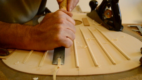 Luthier Making a Guitar Structure with a Chisel