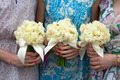 three daffodil wedding bouquets held by bridesmaids