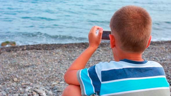 Boy on Beach with Phone 6