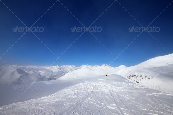 Warning sing on ski slope and snowy mountains in haze - Stock Photo - Images