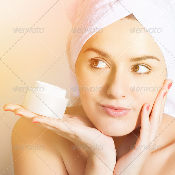 Woman taking care of her skin applying face cream - Stock Photo - Images
