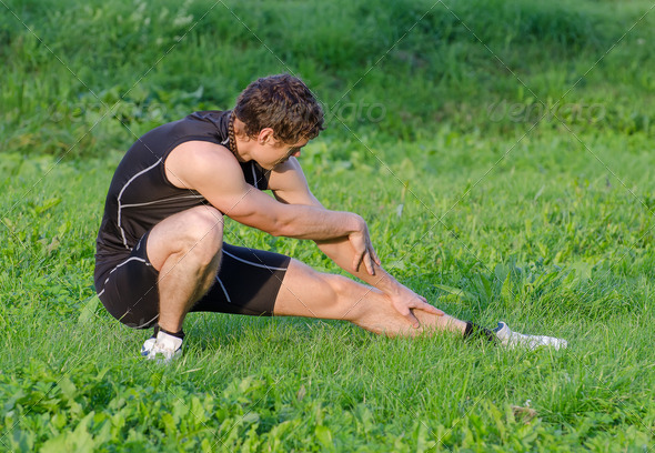 Young sportsman warming up before workout in park - Stock Photo - Images