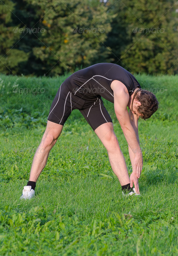 Young sportsman stretching before workout in park - Stock Photo - Images