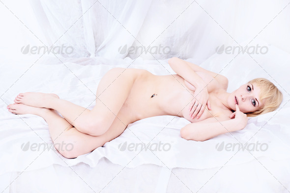 Beautiful naked blonde lying on the bed. - Stock Photo - Images