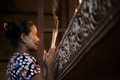 Asian woman praying with incense sticks