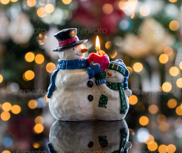 Christmas xmas snowman candle in front of defocus tree lights