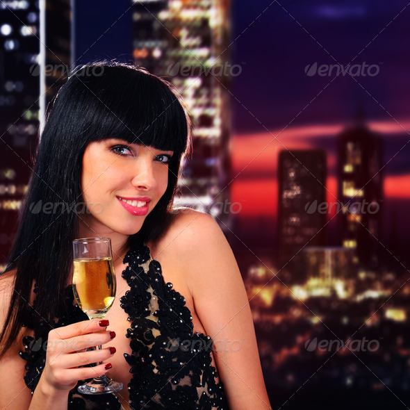 Girl holding a glass of champagne - Stock Photo - Images