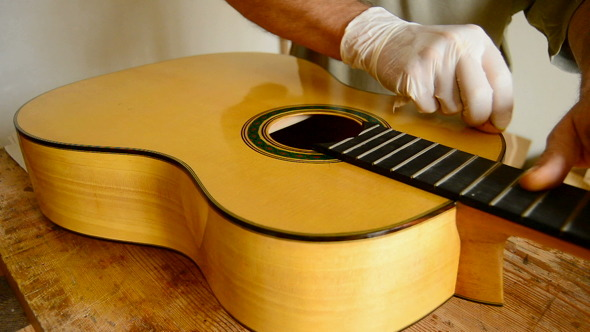 Luthier Varnishing Guitar