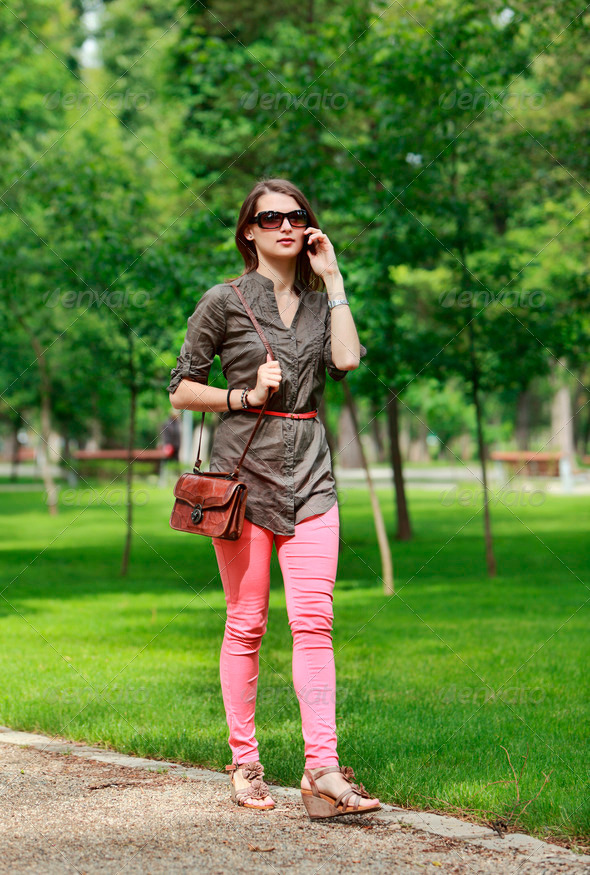 Young Woman on a Mobile Phone Walking in a Park - Stock Photo - Images