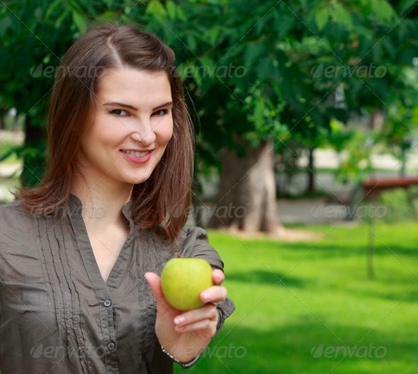 Young Smiling Woman Offering an Apple  - Stock Photo - Images