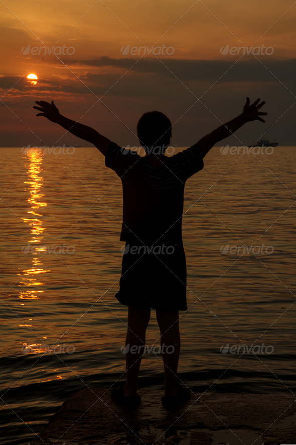 boy at sunset over the sea - Stock Photo - Images