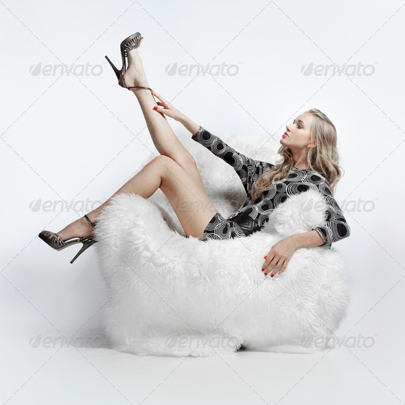 girl sitting in arm-chair - Stock Photo - Images