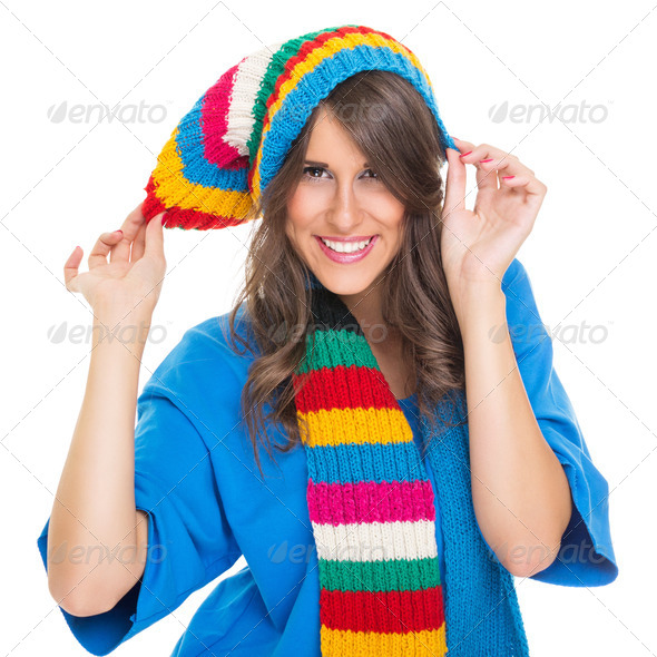 Cute young woman wearing colorful winter hat and scarf - Stock Photo - Images
