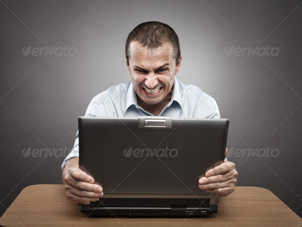 Angry businessman at laptop - Stock Photo - Images