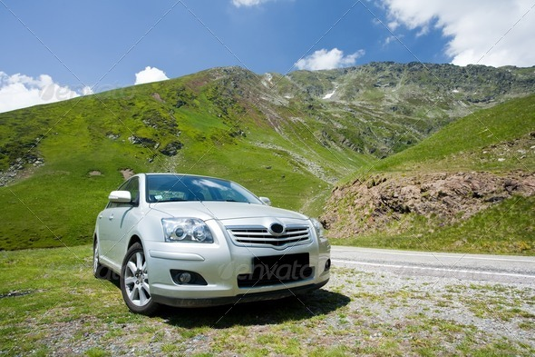 Car parked near a road through mountains - Stock Photo - Images