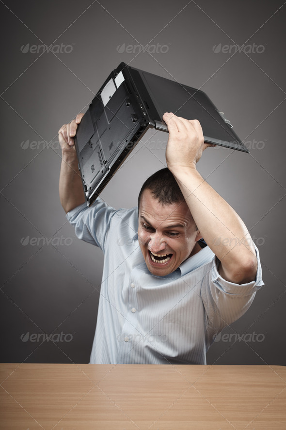 Angry businessman smashing his laptop - Stock Photo - Images
