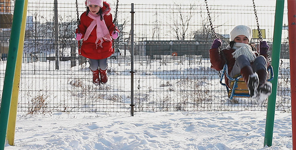 Girls in Swings in Winter Playground