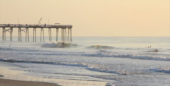 Surfers Catching Waves Near Pier at Sunrise