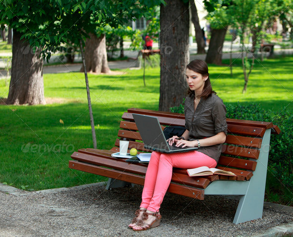Young Woman on Laptop in a Park  - Stock Photo - Images