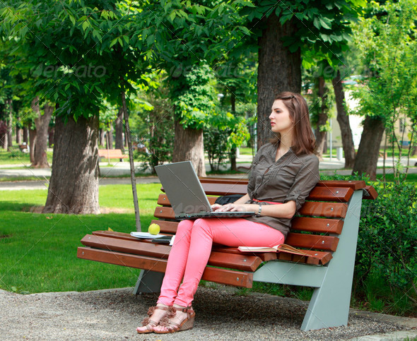 Young Woman Working on a Laptop in a Park - Stock Photo - Images